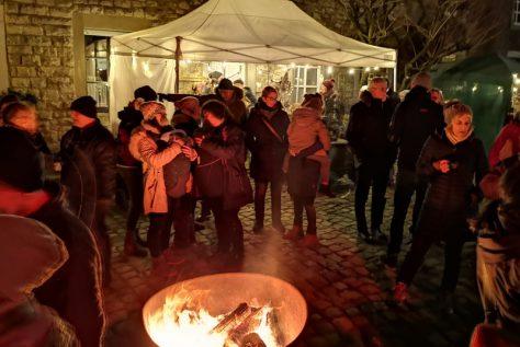 Menschen vor einem wärmendem Feuer auf einem Dorfplatz